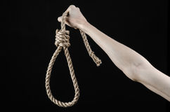 Lynching and suicide theme: man's hand holding a loop of rope for hanging on black isolated background Royalty Free Stock Photos