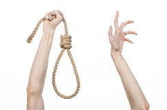 Lynching and suicide theme: man's hand holding a loop of rope for hanging on white isolated background Royalty Free Stock Photo