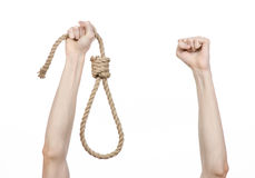 Lynching and suicide theme: man's hand holding a loop of rope for hanging on white isolated background. Studio Stock Photography