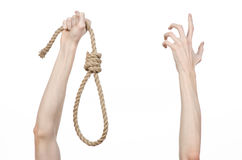 Lynching and suicide theme: man's hand holding a loop of rope for hanging on white isolated background. Studio Stock Images