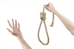 Lynching and suicide theme: man's hand holding a loop of rope for hanging on white isolated background. Studio Stock Photo
