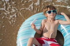 Lyng del muchacho del flotador en la costa Fotos de archivo