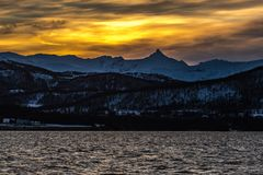 Lyngen alp sunset. The sun sets over Norway`s Lyngen Alps, shot from a boat and enhanced to exaggerate the golden tones of the sky Stock Photography