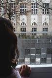 Lynnig dramatisk melankolisk plats av en unge som ser in i ett fönster, Fotografering för Bildbyråer