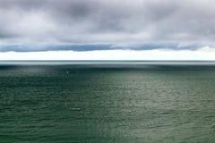 Lynnig flyg- seascape horisont över vatten, moln royaltyfri fotografi