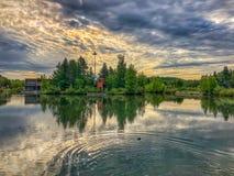 Lynniga moln över en sjö royaltyfri bild