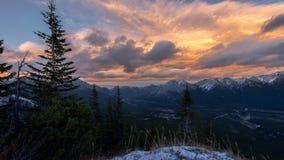 Lynniga moln på solnedgången ovanför steniga berg Arkivfoton