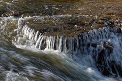 Lynnigt foto av en liten vattenfall arkivfoto