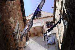 Lynnigt gatahörn med gamla radhus med tvätterit som hänger mellan byggnader - medelhav royaltyfria bilder