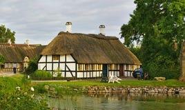 Lyo, Denemarken - Juli vierde, 2012 - Traditionele hout-ontworpen met stro bedekte Deense boerderij met vijver in de voorgrond op Stock Afbeelding
