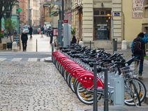 LYON, FRANCE - January 26, 2011: Paved street of overcast winter with parked bicycles with red wheels royalty free stock photography