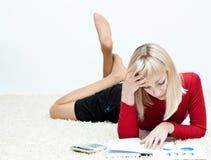 Lyong della ragazza sul pavimento con il calcolatore ed il rapporto Fotografia Stock Libera da Diritti
