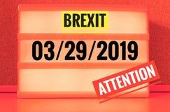 Lysande tecken med inskriften i engelska Brexit och 03/29/2019 och uppmärksamhet, i tysk 29 03 und 2019 Achtung som symboliserar  Arkivfoto