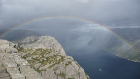 Lyse Fjord with Rainbow. The image shows the Lyse Fjord on a cloudy day from a rock called Preikestolen Stock Photography