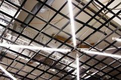 Lysrör hänger på taket i en industribyggnad - på en fabrik Royaltyfri Bild