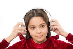 Lyssna för fria nya och kommande schlager just nu Lilla flickan lyssnar trådlös hörlurar för musik Online-musik arkivbild