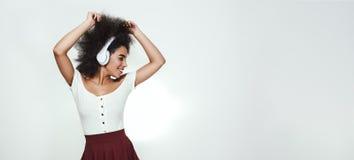 Lyssna hennes favorit- sång Den charmiga afro amerikanska kvinnan som lyssnar till musik och håller ögon, stängde sig, medan stå royaltyfria foton