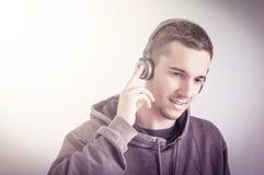 Lyssna till musiken genom att använda hörlurar royaltyfri foto