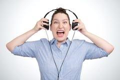 Lyssnande aggressiv musik för emotionell ståendeung flicka i hörlurar arkivfoto