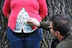 Lyssnande gravid buk för man Arkivbild