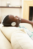 lyssnande koppla av sittande sofa för manmusik till Arkivbild