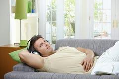 lyssnande le sofa för manmusik till Fotografering för Bildbyråer