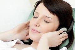 lyssnande liggande teen musiksofa för charmig flicka Royaltyfri Bild