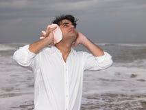 lyssnande man för conch till Arkivbild
