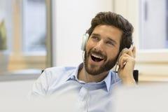 Lyssnande musik för affärsman och sjunga i modernt kontor royaltyfri fotografi
