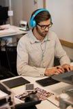 Lyssnande musik för affärsman till och med hörlurar, medan arbeta på det idérika kontoret Royaltyfria Bilder