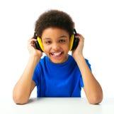 Lyssnande musik för afrikansk amerikanskolapojke med hörlurar med mikrofon Royaltyfri Foto