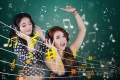 Lyssnande musik för attraktiva flickor Royaltyfria Foton