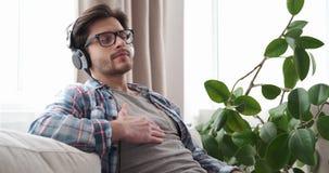 Lyssnande musik för avkopplad man på hörlurar hemma stock video