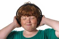 Lyssnande musik för fräknig röd-hår pojke. Arkivfoto