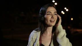 Lyssnande musik för glad flicka med hörlurar på natten arkivfilmer