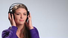 Lyssnande musik för gladlynt nätt kvinna i hörlurar lager videofilmer