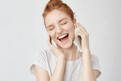 Lyssnande musik för gladlynt rävaktig flickafröjd, i att le för hörlurar arkivfoton