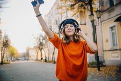 Lyssnande musik för gullig ung flicka i hörlurar och att dansing och rymma mobilephonen i handen, stads- stil, stilfull hipster arkivfoton