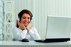 Lyssnande musik för härlig affärskvinna i hörlurar royaltyfria foton