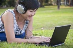 Lyssnande musik för härlig asiatisk kvinna i parken Royaltyfria Bilder