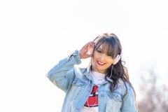 Lyssnande musik för härlig ung flicka utomhus arkivfoto