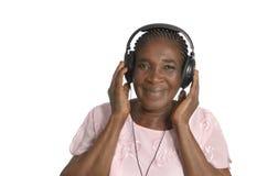 Lyssnande musik för hög afrikansk kvinna med head telefoner Arkivfoton