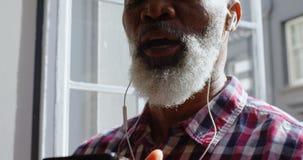 Lyssnande musik för hög manlig ledare på mobiltelefonen 4k stock video