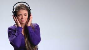 lyssnande musik för hörlurar till den slitage kvinnan stock video