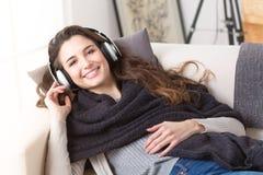 Lyssnande musik för kvinna i hörlurar på en soffa arkivfoto
