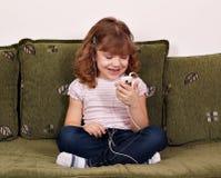 Lyssnande musik för liten flicka Arkivbild