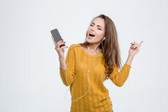 Lyssnande musik för lycklig kvinna i hörlurar Arkivfoto