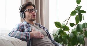 Lyssnande musik för man på hörlurar hemma arkivfilmer