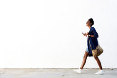 Lyssnande musik för moderiktig svart kvinna på mobiltelefonen royaltyfria bilder