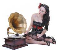 Lyssnande musik för nätt flicka på den gammala grammofonen Arkivfoto
